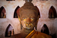 Gold Plated Theravada Buddhist Statues At A Monastery With A Orange Silk Cloth