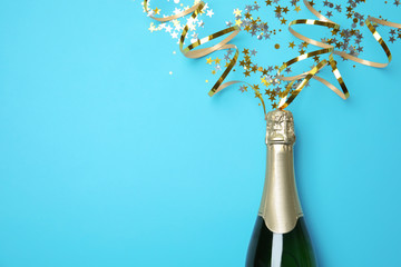 Creative flat lay composition with bottle of champagne and space for text on color background