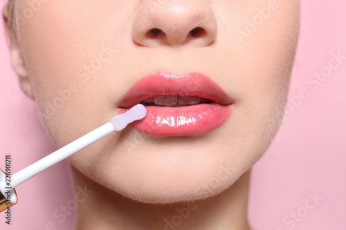 Tablou Canvas Beautiful young woman applying gloss on her perfect lips, closeup