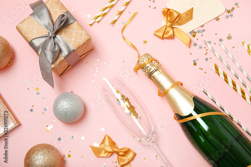 Creative flat lay composition with bottle of champagne and party accessories on color background