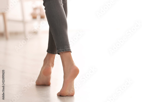 Photo Young woman walking barefoot at home, closeup. Heating concept