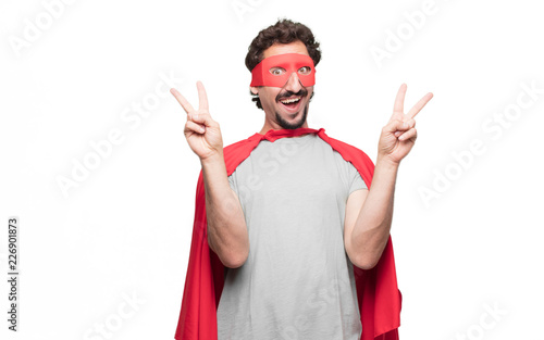 Fotografie, Obraz  Young bearded super hero with a proud, happy and confident expression; smiling and showing off success while gesturing victory with both hands, giving an achiever look, celebrating triumphantly