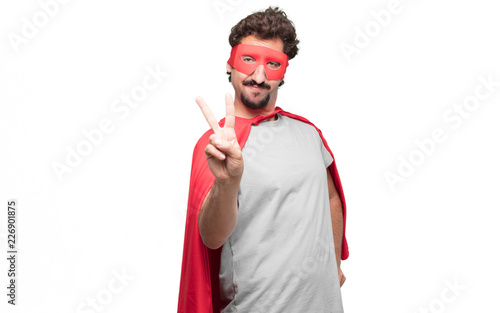 Fotografie, Obraz  Young bearded super hero with a proud, happy and confident expression; smiling and showing off success while gesturing victory, giving an achiever look, celebrating triumphantly