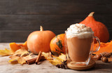 Glass cup with tasty pumpkin spice latte on wooden table