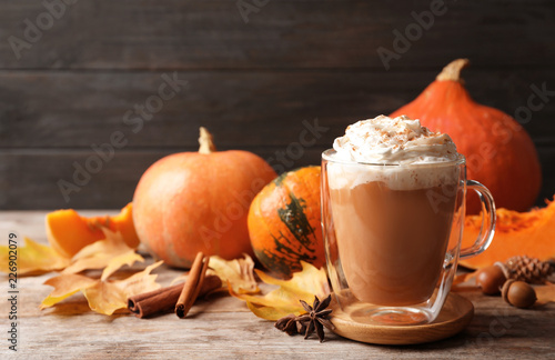 Fotografiet Glass cup with tasty pumpkin spice latte on wooden table