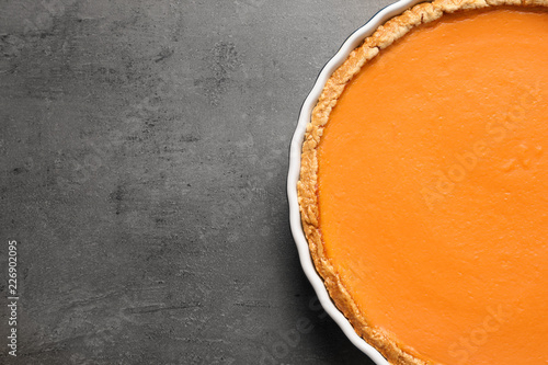 Fresh delicious homemade pumpkin pie on gray background, top view with space for text