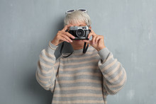 Senior Cool Woman With A Vintage Photography Camera Against Grunge Cement Wall.