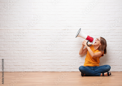 young pretty woman shouting on a megaphone sitting on wooden floor in front a br Fototapeta