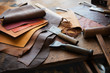 Leather craft or leather working. Selected pieces of beautifully colored or tanned leather on leather craftman's work desk . Piece of hide and working tools on a work table.