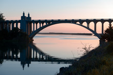 Rogue River Bridge In Gold Beach, Oregon At Sunset Reflected In Water