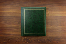 Green Photo Album Or Year Book Cover, Blank, Placed On A Dark Colored Wooden Table.