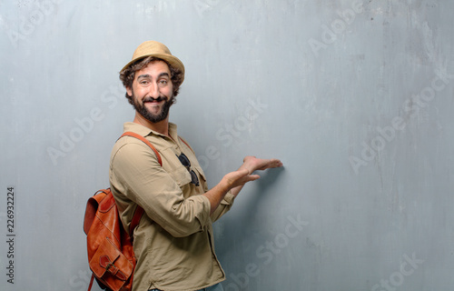 young traveler man or tourist smiling with a proud, satisfied and happy look, welcoming gesture, greeting you Canvas Print