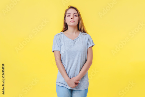Photo Girl on a yellow background is in a closed pose