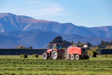A Red Tractor And A Baler Working In A Rural Field In New Zealand Making Hay In The Springtime