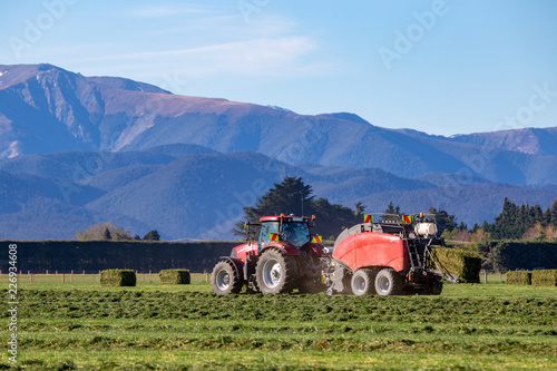 A red tractor and a baler working in a rural field in New Zealand making hay in Canvas Print