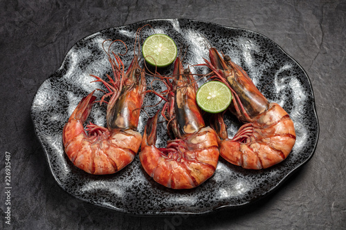 Three jumbo shrimps for dinner on dark plate. Food background. Top view.