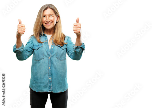 Fotografie, Obraz  senior beautiful woman with a satisfied, proud and happy look with thumbs up, signaling OK with both hands, sending a positive, alright' message