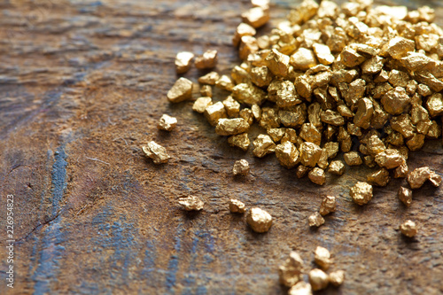 Fotografia, Obraz  Mound of gold on a old wooden work table