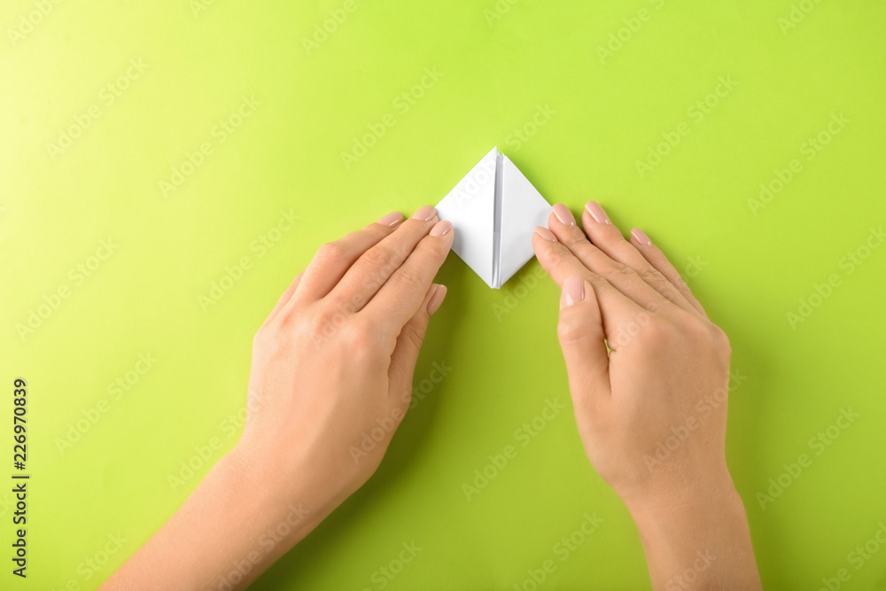 Fototapety, obrazy: Woman making origami boat on color background