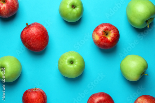 Different ripe fresh apples on color background