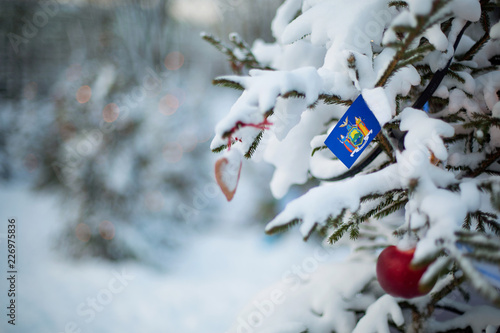 new york state flag christmas background outdoor christmas tree covered with snow and decorations