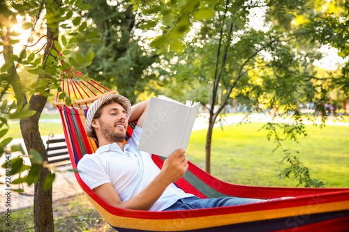 Handsome young man with book resting in hammock outdoors Canvas Print
