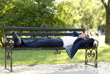 Handsome Young Businessman Resting On Bench In Park