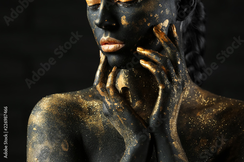 Beautiful woman with black and golden paint on her body against dark background, Wallpaper Mural