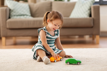 Fototapeta childhood and people concept - happy three years old baby girl playing with toy car at home