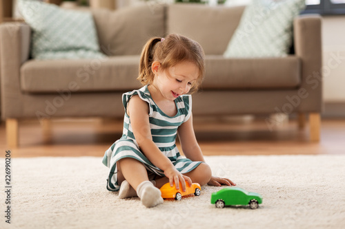 childhood and people concept - happy three years old baby girl playing with toy car at home