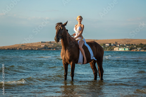 Foto op Aluminium Ontspanning beautiful young woman in white dress by the sea with horse