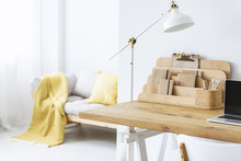 White Lamp On Wooden Desk With Laptop In Bright Freelancer's Interior With Organizer. Real Photo