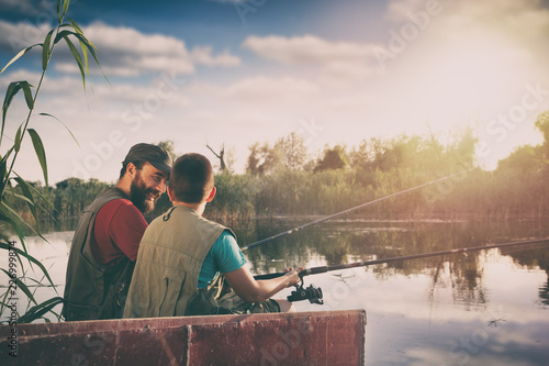 father and son sitting in boat on lake while fishing together