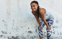 Young Smilng Woman During A Break Outdoors Against Concrete Wall. Happy Athletic Female Relaxing After Exercises, Looking At The Camera, Resting After Workout Outside.