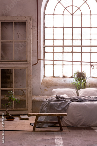 Papiers peints Akt Real photo of a wabi sabi bedroom interior with a big, old window and bed