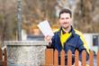 Briefträger reicht Briefe über den Zaun