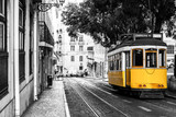 Yellow tram on old streets of Lisbon, Portugal, popular touristic attraction and destination. Black and white picture with a coloured tram. - 227014006