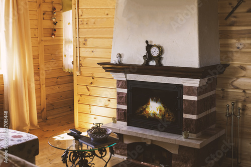 Canvas Print A cozy living room with a fireplace by the sofa and a forged table