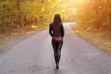 Fototapeta Uliczki - Pretty woman walking on the road