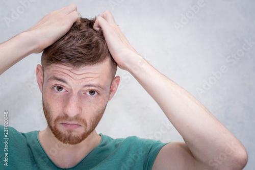 Fotografie, Obraz  Young man tears hair on his head from annoyance. Closeup portrait