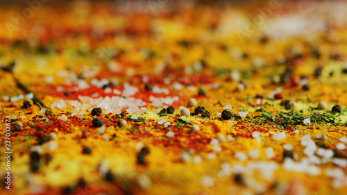 Closeup shot of various fresh spices spilled on surface of timber tabletop in ki Fototapet