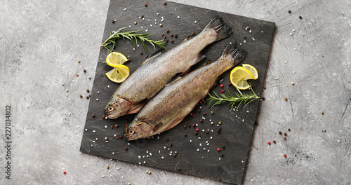 Fotomural From above view of fresh trout decorated with slices of lemon and herb placed on