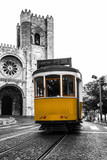 Yellow tram against the Lisbon Cathedral in Alfama district of Lisbon, Portugal. Black and white photo with coloured tram - 227037401