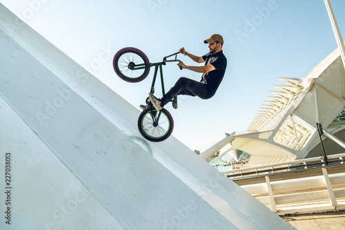 Photo Young man doing street tricks with a bmx
