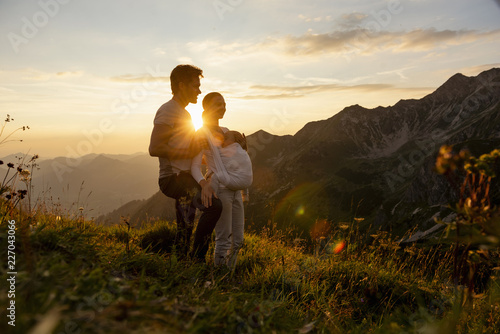 Germany, Bavaria, Oberstdorf, family with little daughter on a hike in the mountains at sunset