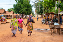 Togoville Village In Togo. Women Walking In African Outfits In The Village. Voodoo Religion In Togo, West Africa. Togoville And Lomé Voodoo Markets.