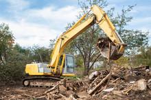 Excavator Bucket Loading Construction Debris After Demolishing House
