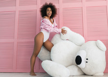 Smiling African American Woman With Beautiful Face And Curly Hairstyle In Pink Denim Jeans Jacket And Sexy Lingerie Hugging Large Plush  Bear Toy. Birthday Present For Positive Dark Skinned Female.