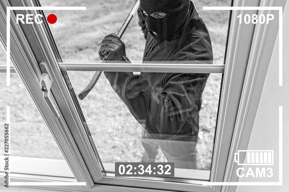 Fototapeta CCTV view of burglar breaking in to home through window
