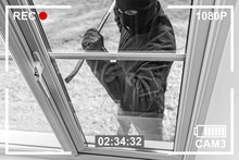 CCTV View Of Burglar Breaking In To Home Through Window